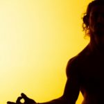 The silhouette of man practicing yoga in the sunset light